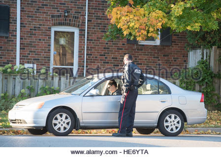Toronto, Ontario, Canada, A traffic police officer working in an urban area. Lady in a white parked car looking - Stock Photo