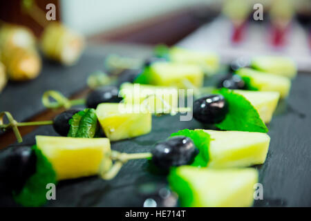Blured cater canapes with pinapple and grapes on black table - Stock Photo