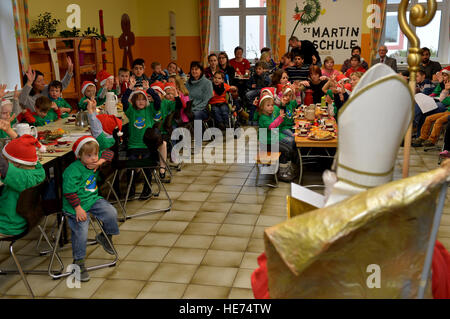 Sankt Nikolaus sits on a golden chair and reads to children from St. Martin School in Bitburg, Germany, Dec. 8, - Stock Photo