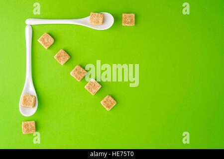 Brown sugar cubes and white spoons on greenery background arringed in rows. Top view. Flat lay. Copy space for text. - Stock Photo