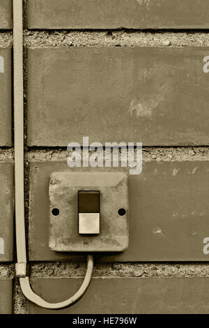 Outdoor electric equipment control industrial button switch wire cable closeup, old aged weathered grungy brick - Stock Photo