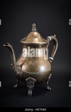 Old silver kettle utensils on black background - Stock Photo