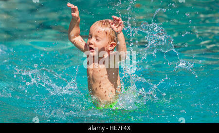 Funny photo of active baby boy splashing in swimming pool with fun, jump deep down underwater. - Stock Photo