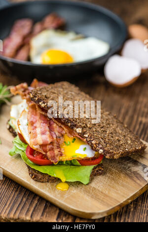 Wooden Table with Bacon and Eggs (selective focus; close-up shot) - Stock Photo
