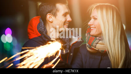 Beautiful couple with sparklers on street in evening - Stock Photo
