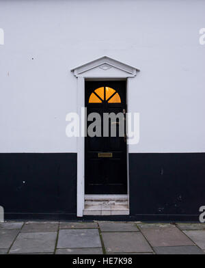Black wooden Victorian door on a black and white wall with glass panel on top and warm yellow light coming from - Stock Photo