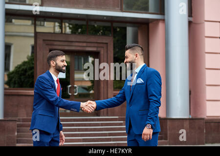 Two arab men greeting each other they are familiar they rub their two saudi men greeting each other nice to meet you two arab businessman handshaking in front of the business center smiling m4hsunfo