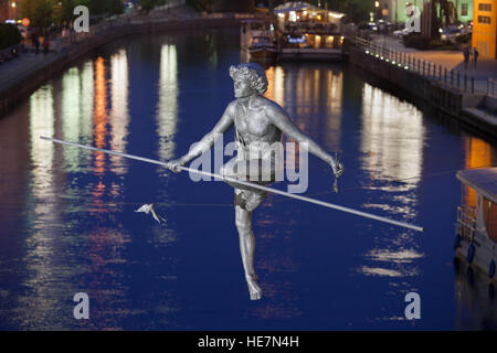 'Man crossing the River' at night, balancing sculpture by Jerzy Kedziora in Bydgoszcz, Poland, commemorates the - Stock Photo