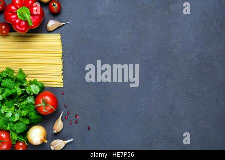 Pasta, spices and vegetables on slate background - cooking ingredients for italian cuisine. Copy space for text. - Stock Photo