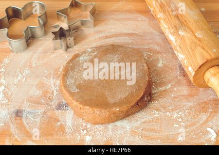 Gingerbread cookie dough, rolling pin, cookie cutters and flour on wooden table. Preparation of gingerbread cookie - Stock Photo