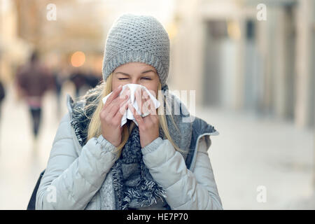 Woman with a seasonal winter cold blowing her nose on a handkerchief or tissue as she walks down an urban street - Stock Photo