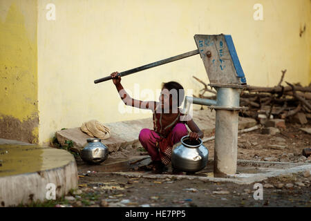 Indian village girl smiling and plumbing borewell for water - Stock Photo
