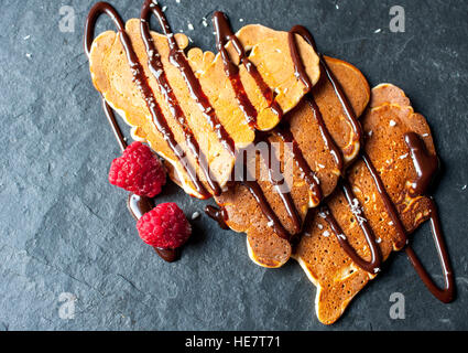 Pancakes in the shape of a heart with chocolate syrup and raspberries on valentine's day. - Stock Photo
