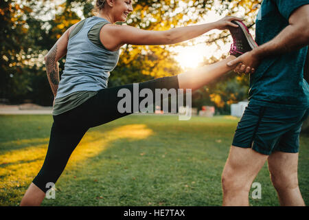 Fit young woman doing stretching exercises with the help of a personal trainer in park. Coach holding leg of female. - Stock Photo