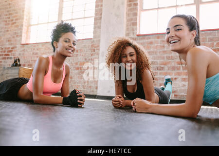 Portrait of three young women in fitness class looking at camera and smiling. Female friends exercising together - Stock Photo