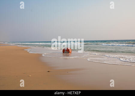 A red oil drum is washed ashore at the yellow beach - Stock Photo