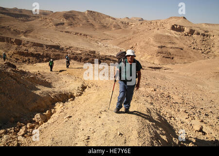 A 79 year old senior citizen man hiker is leading other hikers walking up above Nachal or Nahal Marzeva in the Negev - Stock Photo