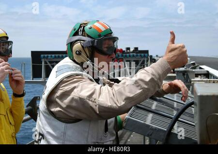 U.S. President George W. Bush gives a thumbs-up to aircraft preparing to launch from the flight deck aboard the - Stock Photo