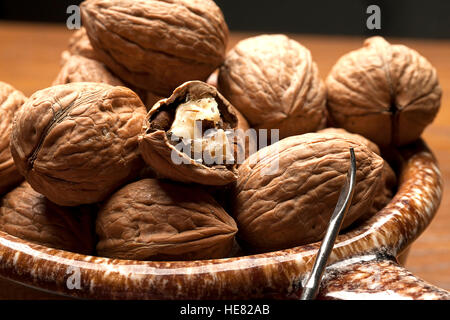 Mostly unshelled walnuts in bowl. - Stock Photo
