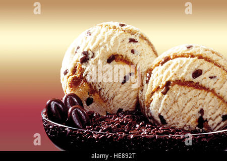 Two scoops of mocca-flavoured ice cream on chocolate chips - Stock Photo