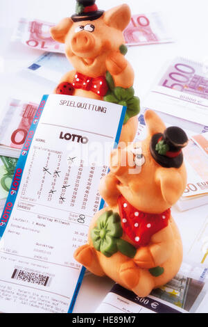 Pigs, lucky charms, sitting on euro bills with a lottery ticket - Stock Photo