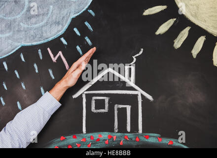 Mens hand protects a house - Stock Photo