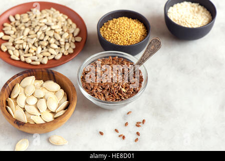 Assorted oil seeds (flax, sesame, pumpkin, sunflower, mustard) in small bowls on stone background - organic ingredients - Stock Photo