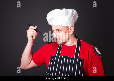 Portrait of a funny cook with a ladle in his hand in the studio on a black background - Stock Photo