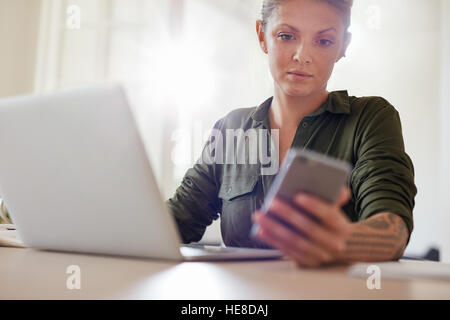 Shot of attractive young woman sitting at table with laptop and reading text message on his mobile phone - Stock Photo