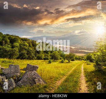 Winter meets spring composite landscape. Valley with trees and boulders on a grass. Road through meadow goes to - Stock Photo