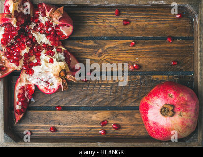 Fresh ripe pomegranates, one cut in pieces in wooden tray - Stock Photo