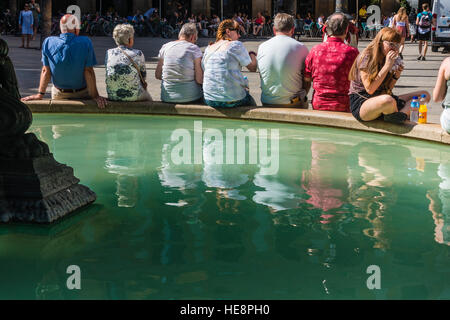 A row of tired tourists sit side-by-side on the edge of a fountain, reflecting water, to relax in a plaza in Barcelona, - Stock Photo