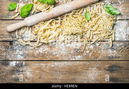 Various homemade fresh uncooked Italian pasta on wooden background - Stock Photo