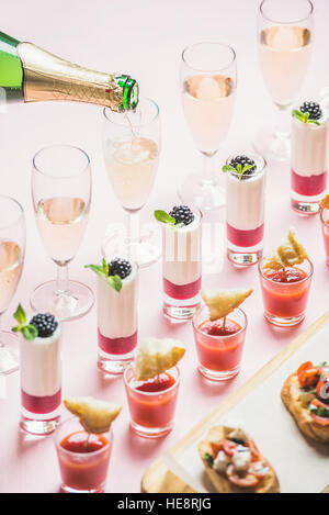 Various snacks, brushettas, gazpacho shots, desserts, champagne pouring to glasses - Stock Photo