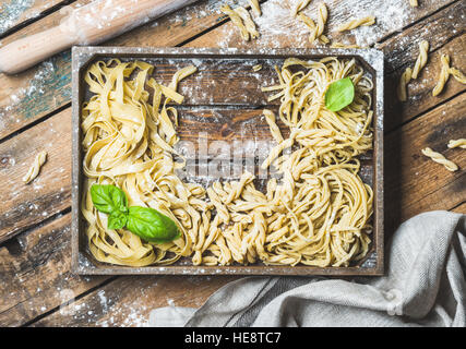 Various uncooked Italian pasta in wooden tray with basil leaves - Stock Photo