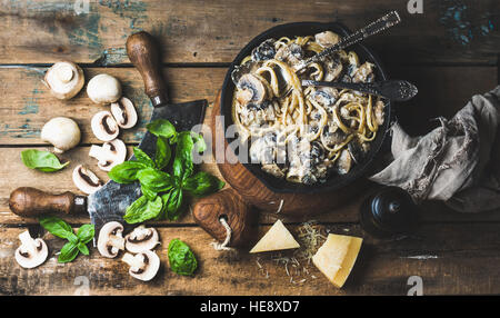 Mushroom pasta spaghetti in iron pan served with parmesan, basil - Stock Photo