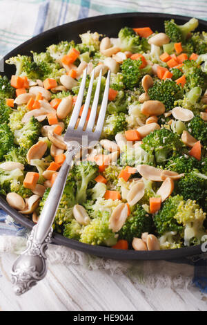 Dietary salad with broccoli, carrots and peanuts close-up on a plate. vertical - Stock Photo