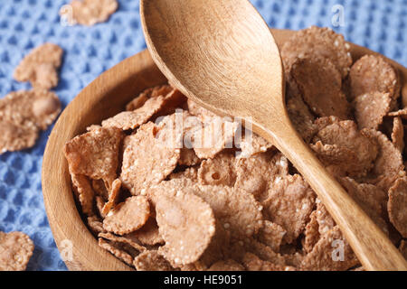 Dietary breakfast: bran flakes in a wooden bowl closeup. horizontal, rustic style - Stock Photo
