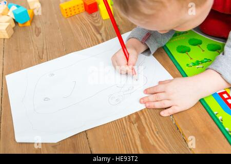 Little child drawing with pencil on white paper. Close up of toddler playing on floor. - Stock Photo