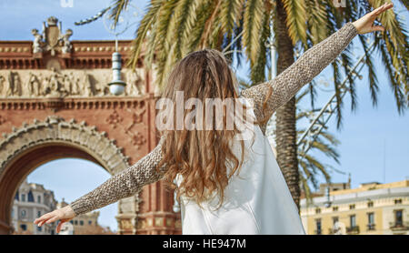 in Barcelona for a perfect winter. Seen from behind cheerful young fashion-monger in earmuffs in Barcelona, Spain - Stock Photo