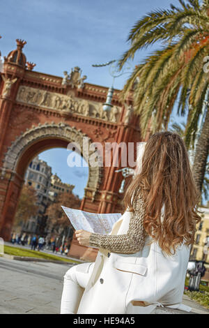 in Barcelona for a perfect winter. Seen from behind young woman in earmuffs near Arc de Triomf in Barcelona, Spain - Stock Photo