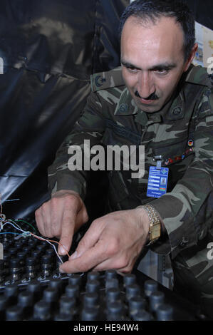 Azerbaijan Maj. Rauf Akhundov, telephone switch operator, connects the cables of a junction box for interoperability - Stock Photo