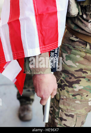 A U.S. Air Force Airman assigned to the 83rd Expeditionary Rescue Squadron holds a U.S. flag bearing the names of - Stock Photo