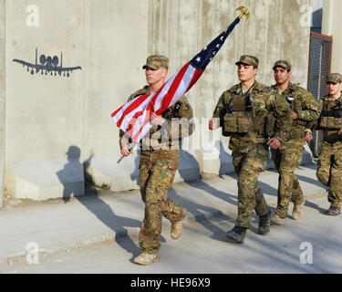 A multiservice formation of special operators runs with a U.S. flag bearing the names of seven special operators - Stock Photo