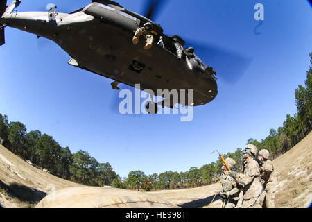 Soldiers assigned to 1st Brigade Combat Team, 82nd Airborne Division, brace the rotor wash of UH-60 Black Hawk descending - Stock Photo