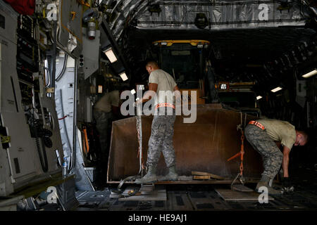 Airmen from the 8th Expeditionary Air Mobility Squadron make final checks while securing a bulldozer onto a -17 - Stock Photo