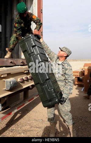 U.S. Air Force Capt. Matthew Vincent helps a member of the Afghan National Army (ANA) off load NATO weapons at the - Stock Photo
