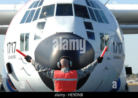 A U.S. Air Force crew chief directs a Coast Guard C-130 on the flight line at Homestead Air Reserve Base, Jan 20, - Stock Photo