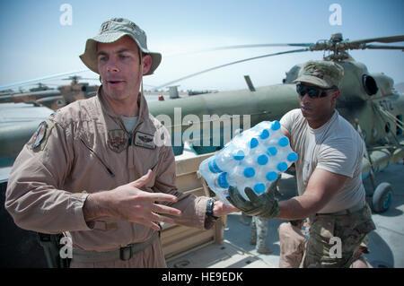 U.S. Air Force Capt. Adam Ackerman, MI-17 pilot advisor, 441st Air Expeditionary Advisory Squadron, passes a pack - Stock Photo
