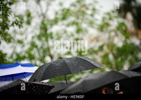 Umbrellas come out as it begins to rain at the farewell tribute for Joint Chiefs of Staff Vice Chairman Gen. James - Stock Photo